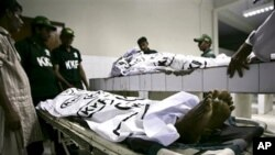 Pakistani rescue workers gather around bodies of shooting victims at a local hospital in Karachi, 17 Oct. 2010.