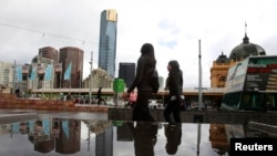 FILE - Office workers walk through Federation Square in Melbourne, Australia, May 11, 2011. Police say suspected terrorists now under arrest had planned to attack the square and other targets.