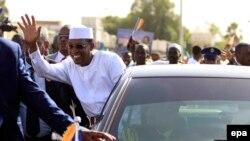 Le président tchadien Idriss Deby se penche de sa voiture pour saluer la foule après son arrivée à Khartoum, Soudan, 08 mars 2016. Deby a été proclamé vainqueur au premier tour de l'élection présidentielle du 10 mars 2016 au Tchad avec plus de 69%. epa/MORWAN ALI