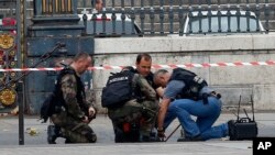 Polisi Perancis memeriksa peringatan adanya bom di depan gedung pengadilan di Paris, Senin (16/11). Pihak berwenang Perancis telah menahan 23 orang dalam sejumlah razzia di seluruh negara itu pasca serangan di Paris Jumat (13/11) malam.
