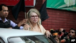 FILE - Bangladesh's former Prime Minister Khaleda Zia holds a black flag as she stands at her office in Dhaka, Jan. 5, 2015. A court issued an arrest warrant for Zia on March 30, 2016, over the 2015 fire-bombing of a bus that killed two people and injured many others.