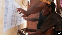 People look for their names on the electoral roll before casting their ballot at a polling station in Lome, Togo, April 25, 2015.