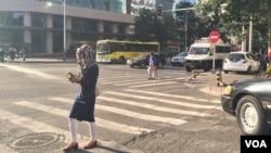 乌鲁木齐街头有妇女边走边看手机(2015年3月,VOA图片)