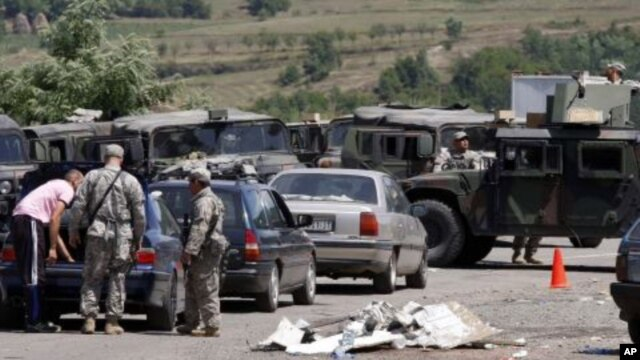 US soldiers serving in KFOR check vehicles from Serbia entering Kosovo after reopening a checkpoint, demolished and burned by angry Kosovo Serbs, in the village of Jarinje, on the Serbia-Kosovo border, July 28, 2011