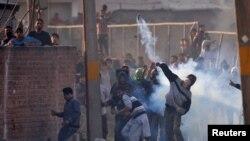 سری نگر میں مظاہریں کا ایک گروپ ، بھارتی فوجی دستوں کی کشمیر میں آمد کی 70 سالگرہ کے موقع پر اشک آور گیس کا مقابلہ پتھراؤ سے کر رہا ہے۔ 27 اکتوبر 2017