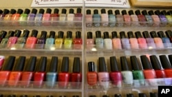 FILE - A wall rack is filled with nail polishes, Nov. 30, 2016, at a salon in Alameda, Calif. A group of Vietnamese-American salon owners in Louisiana accused the state of racial bias and received a $100,000 settlement.