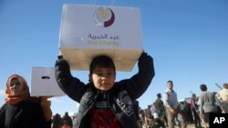 Iraqi citizens who fled the fighting between Islamic State militants and the Iraqi forces, carry aid supplies. Nov. 21, 2016.