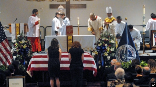 Women bow before the casket of slain U.S. Immigration and Customs Enforcement (ICE) Special Agent Jaime Jorge Zapata during a funeral mass at the Brownsville Events Center in Brownsville, Texas, February 22, 2011