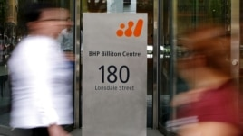 Pedestrians pass the head offices of mining giant BHP Billiton in Melbourne, Australia November 27, 2008 (file photo).