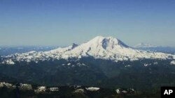Mount Rainier stands in the foreground, framed in the background by Mount Adams, far left, Mount Hood, second left, and Mount St. Helens, right, in this aerial view