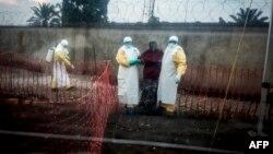 Un patient atteint d'Ebola est conduit par deux travailleurs médicaux dans une unité de soins d'urgence Biosecure (CUBE), à Beni, le 15 août 2018.