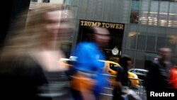 FILE - Pedestrians are seen in a slow shutter speed photograph as they pass Trump Tower on 5th Avenue in New York City, April 26, 2017.