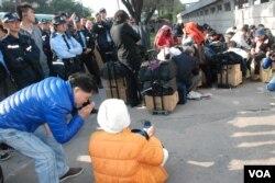 一名女示威者坐在地上,攔阻水貨客進入上水火車站,有便衣警員上前勸籲她讓路