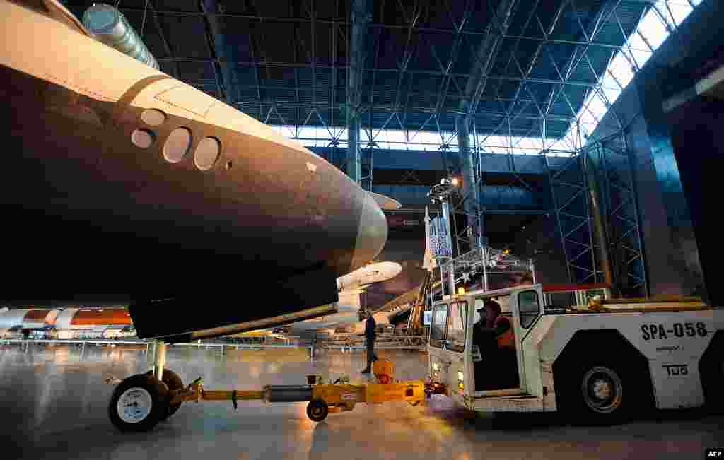 Space Shuttle Enterprise is prepared to be rolled from the Space Hangar at the Steven F. Udvar-Hazy Center prior to a transfer ceremony, in Chantilly, Virginia. (NASA/Paul E. Alers)