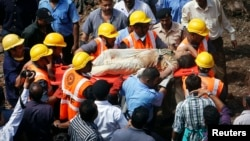 Rescue workers use a stretcher to carry a woman who was rescued from the rubble at the site of a collapsed residential building in Mumbai, Sept. 27, 2013