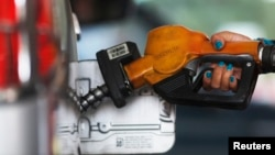 Petugas SPBU Pertamina sedang mengisi bensin ke sebuah mobil, 17 November 2014.