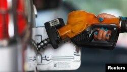 Seorang petugas pom bensin Pertamina di Jakarta mengisi bensin mobil (17/11).