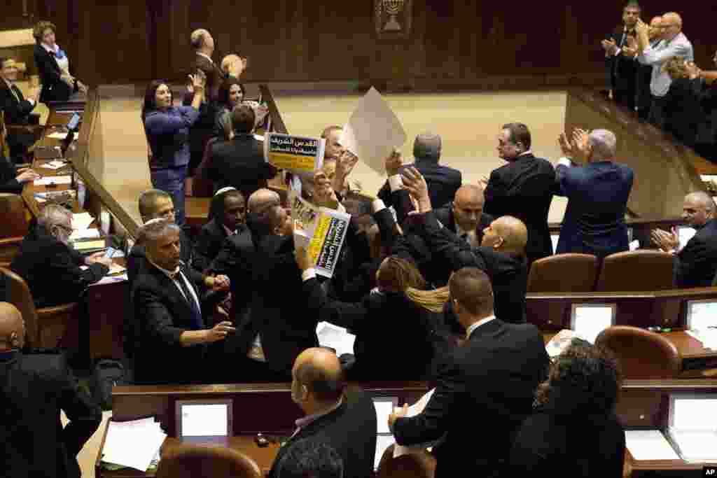 Israeli Arab members hold signs in protest as security pushes them out as U.S. Vice President Mike Pence speaks in Israel's parliament in Jerusalem.