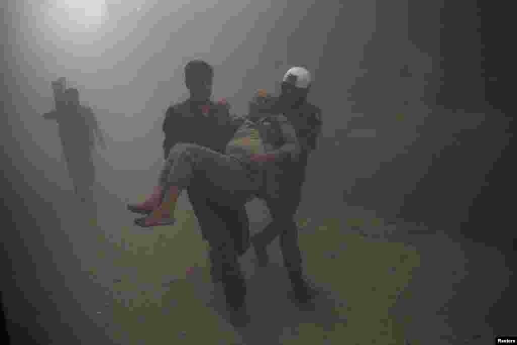 گروه امداد مردمی، مردی که در حملات هوایی به حلب مجروح شده را منتقل می کند.