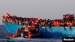 2016年8月29日利比亚海岸救助艇接近一个挤满移民的木船实施援救。