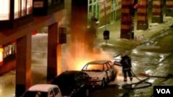 Gambar yang diambil dari video ini menunjukkan petugas pemadam kebakaran menyiram air ke atas mobil yang telah meledak, di pusat kota Stockholm.
