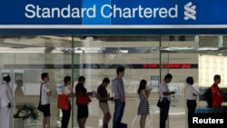 People queue up outside a Standard Chartered Bank branch before operation hours at the central business district in Singapore January 23, 2014. Standard Chartered's Chief Executive Peter Sands said takeover talk that has resurfaced around his bank after r