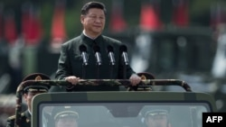File - China's President Xi Jinping inspects the People's Liberation Army. Tanks, missile launchers and chanting troops greeted Xi in a potent display of Chinese military strength.
