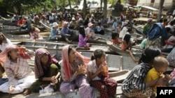 Dân chúng trong tỉnh Kandal, cách thủ đô Phnom Penh, khoảng 50 kilomet, ngồi trên thuyền chờ nhận lương thức cứu trợ cho nạn nhân lụt