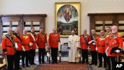 FILE - Pope Francis, flanked at left by Grand Master of the Knights of Malta Matthew Festing, stands during a family photo at the Vatican, Thursday, June 23, 2016