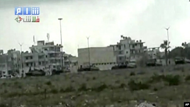 This image made from amateur video and released by Shams News Network and accessed via The Associated Press Television News on Saturday, Aug. 13, 2011, shows a long shot of military vehicles lined up on road, backdrop of buildings taking up positions near