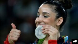 FILE - United States' Aly Raisman displays her silver medal for floor during the artistic gymnastics women's apparatus final at the 2016 Summer Olympics in Rio de Janeiro, Brazil, Tuesday, Aug. 16, 2016.