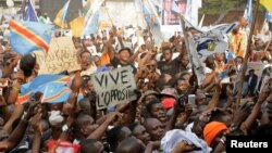 FILE - Supporters of Congolese opposition leader Etienne Tshisekedi carry placards and flags as they attend a political rally in the Democratic Republic of Congo's capital Kinshasa, July 31, 2016.