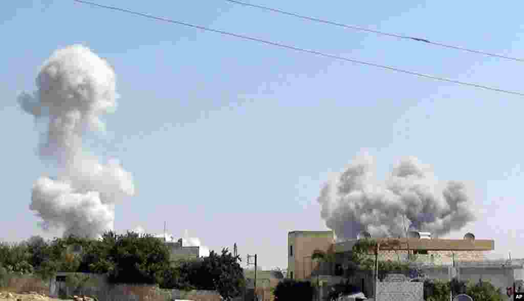 In this citizen journalism image provided by Edlib News Network, ENN, smoke rises after explosives were dropped by a Syrian government warplane in Idlib province, August 30, 2013.