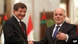 伊拉克總理阿巴迪(右)與土耳其總理達武特奧盧在巴格達握手。(2014年11月20日)
