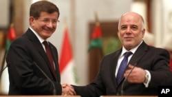 Irak başbakanı el-Abadi geçen Kasım ayında Bağdat'ı ziyaret eden Başbakan Davutoğlu ile el sıkışırken