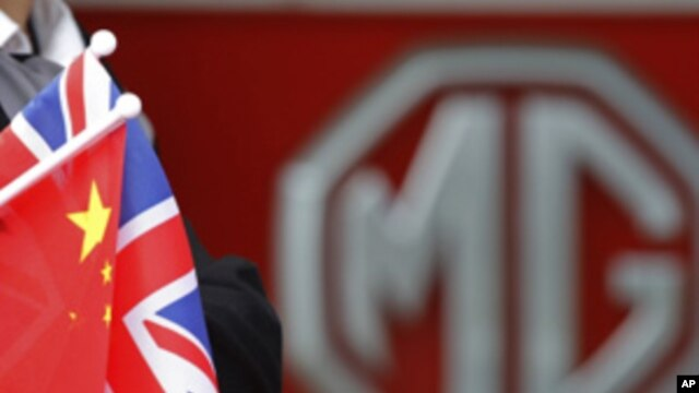 An MG employee holds Chinese and British flags during a visit by Chinese Premier Wen Jiabao to the MG motor plant in Birmingham, central England, Sunday, June 26, 2011.
