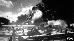 La histórica imágen muestra a los marineros caminando entre los restos de los aviones en la base de la fuerza aérea naval de Ford Island, mientras llamas emergen del USS Shaw durante el ataque contra Pearl Harbor, el 7 de diciembre de 1941.