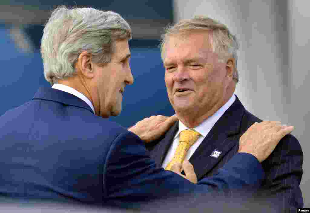 U.S. Secretary of State John Kerry rests his hands on the shoulders of Australian Ambassador to the U.S., Kim Beazley, upon his arrival in Sydney, Aug. 11, 2014.