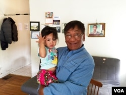 Chhiv Chhy, 63, a client of the mental health community organization CERI that helps former refugees in San Francisco Bay area holds his granddaughter after an interview with VOA Khmer at his home in Oakland, August 31, 2016.