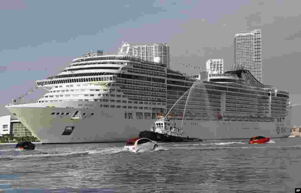 The MSC Divina cruise ship arrives at the Port of Miami, Florida, USA, escorted by a fleet of Fiat 500 watercrafts.