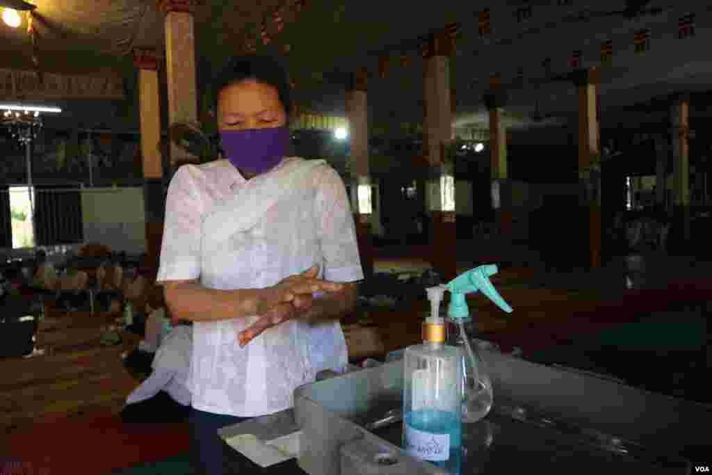 A woman cleans her hands with a disinfecting spray at Thann pagoda, Phnom Penh, Cambodia, Tuesday, April 14, 2020. (Kann Vicheika/VOA Khmer)