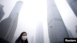 A woman wearing a mask walks past below skyscrapers amid heavy smog at the financial district of Pudong, in Shanghai, China, Dec. 11, 2015.