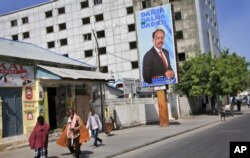 Somalis walk past a campaign poster for candidate Mohamed Abdullahi Farmaajo on the eve of presidential elections in Mogadishu, Somalia, Feb. 7, 2017. Graft - vote-buying, fraud, intimidation - is the top concern in a nation that Transparency International now rates as the most corrupt in the world.
