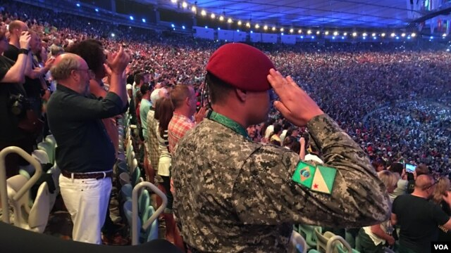 A military policeman salutes as Brazil's national anthem is performed at the start of the opening ceremonies of the 2016 Rio Olympic Games, Aug. 5, 2016, in Rio de Janeiro, Brazil. (P. Brewer/VOA)