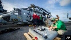 Para awak kapal induk AS menyiapkan helikopter Sea Hawk di atas kapal induk AS USS George Washington untuk operasi bantuan di Filipina (13/11).