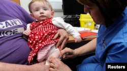 FILE - Lauren Durbin, aged 10 months, is given an MMR injection by Sister Sian Owen at the Paediatric Outpatients department at Morriston Hospital in Swansea, south Wales, April 6, 2013.