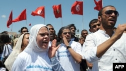 FILE - About 100 unemployed people with university degrees demonstrated outside Tunisia's Kasbah government building in Tunis, May 24, 2012.
