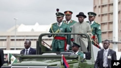 Nigerian president Goodluck Jonathan (right) stands with military aides in a parade convoy during Army Day celebrations in the capital Abuja, 6 Jul 2010 (File Photo)
