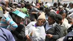 A woman seeks shade beneath her ID documents as she joins about 200 Zimbabweans in a queue outside the Home Affairs offices in downtown Johannesburg, 6 Oct 2010.