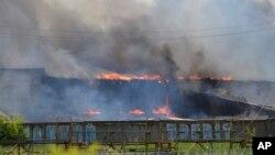 Asap hitam mengepul dari pabrik furniture yang terbakar pasca serangan mortir pasukan Ukraina di Slovyansk, Ukraina timur (8/6).